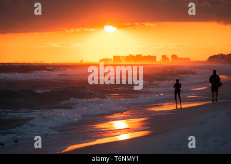 Young couple watching dramatic orange red sunset in Santa Rosa Beach, Florida with Pensacola coastline coast skyline in panhandle with ocean gulf of m - Stock Photo