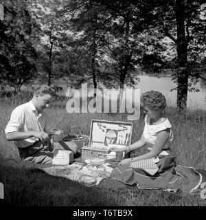 Picnic in the 1950s. A young couple are enjoying a sunny day. They have packed their food and drinks in the practical picnic case and are sitting on a blanket in the sun eating and drinking. Sweden 1956 - Stock Photo
