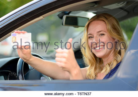 Young blond woman showing off her drivers license - Stock Photo