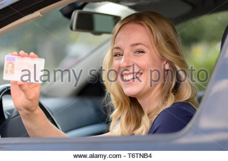 Happy young woman showing off her drivers license - Stock Photo