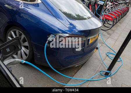 A blue Tesla Model S car recharges its batteries from a street recharging point provided by pay-to-use Polar Network from an Elektrobay charge point in St. James's Square, on 29th April 2019, in London, England. - Stock Photo