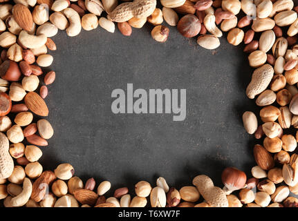 Frame made of different nuts on grey background - Stock Photo