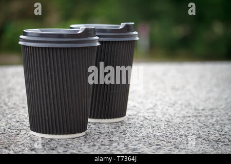 Two black disposable cups of coffee with lids are standing on the stone parapet, rest and a walk around the city, background or concept - Stock Photo