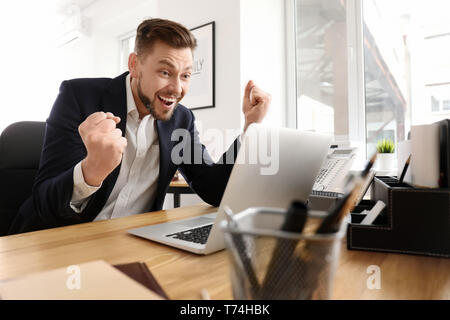 Happy excited businessman with laptop in office - Stock Photo