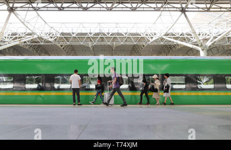 (190504) -- SHANGHAI, May 4, 2019 (Xinhua) -- Passengers prepare to get on board the bullet train D5687 heading for Jinhua of neighboring Zhejiang Province from Shanghai South Railway Station, in Shanghai, east China, May 4, 2019. Two more CR200J bullet trains are assigned to Shanghai train depot by China Railway Shanghai Group Co. to cope with the travel rush during the May Day national holiday. (Xinhua/Fang Zhe) - Stock Photo