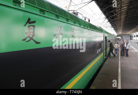 (190504) -- SHANGHAI, May 4, 2019 (Xinhua) -- Passengers get on board the bullet train D5687 heading for Jinhua of neighboring Zhejiang Province from Shanghai South Railway Station, in Shanghai, east China, May 4, 2019. Two more CR200J bullet trains are assigned to Shanghai train depot by China Railway Shanghai Group Co. to cope with the travel rush during the May Day national holiday. (Xinhua/Fang Zhe) - Stock Photo