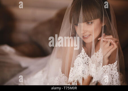 Portrait of charming bride sitting on the bed in a hotel room. the bride is covered with veil. Close up. Wedding morning. Gentle, Tender emotion on th - Stock Photo