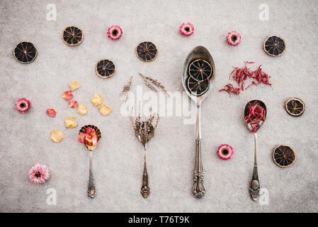 Herbs, flowers, dried lemon slices and vintage silver spoons on concrete background. - Stock Photo