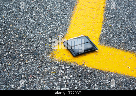 Wallet with money drop on the street and lost - Stock Photo