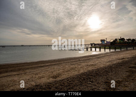 Southend-on-Sea March 2019, Essex, UK. Seafront against the sun and cloudy sky at sunset. - Stock Photo