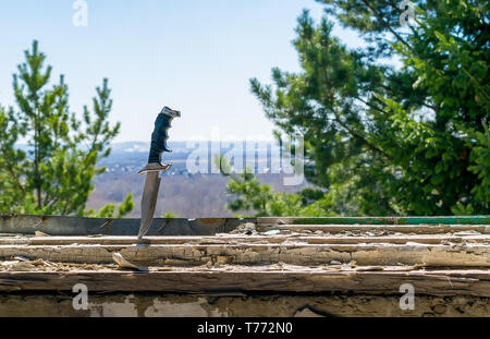 a terrible old combat knife stuck in the ruined window sill of an abandoned house on the background of green leaves of a coniferous tree and outline t - Stock Photo