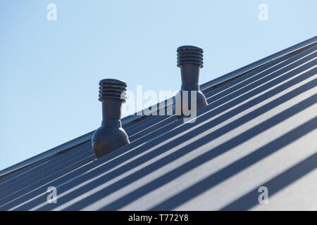 Exhaust pipe on the private house roof. - Stock Photo
