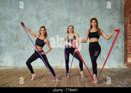 Three smiling beautiful, fitness girls posing in a fitness room. Concept sport, teamwork. Gray background - Stock Photo