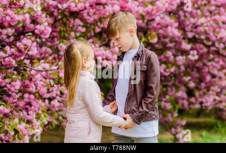 Romantic date in park. Spring time to fall in love. Kids in love pink cherry blossom. Love is in the air. Couple adorable lovely kids walk sakura garden. Tender love feelings. Little girl and boy. - Stock Photo