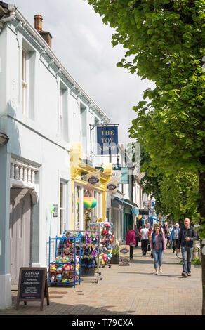 Couple walking past shops along Cockermouth Main street, Cumbria, England, UK - Stock Photo