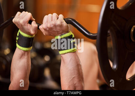 Handsome young muscular man close up, doing bench french press workout with barbell in gym . - Stock Photo