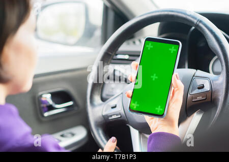 Young female driver using touch screen smartphone in a car. green chroma key on the phone display. - Stock Photo