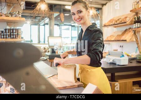 Shop clerk in deli cutting cheese - Stock Photo
