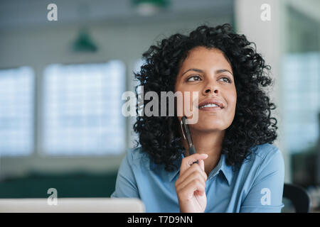 Smiling young businesswoman deep in thought at her office desk - Stock Photo