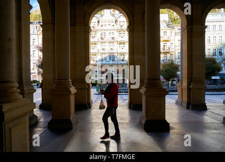 a tourist walking through the popular Mill Colonnade in the Old Town of Karlovy Vary in the Czech Republic - Stock Photo