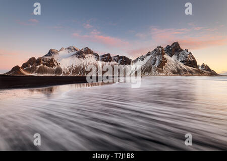 Person standing as a scale in the rolling waves at Vestrahorn. - Stock Photo