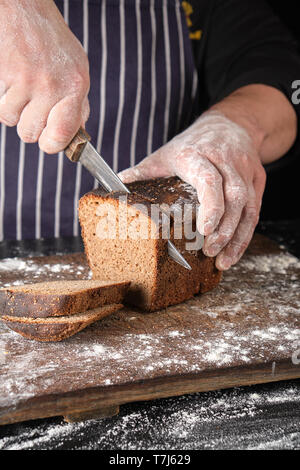 chef in black uniform holds a kitchen knife in his hand and cuts off pieces of bread from a baked brown rye flour loaf on a wooden board - Stock Photo