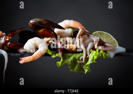 Seafood with salad and lime slices on a black background. - Stock Photo