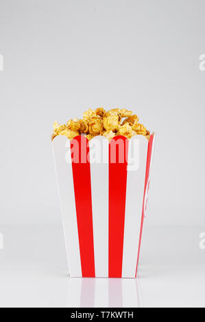 Caramel popcorn in striped paper red and white line box on white  background. Snack  and food for a movie.Vertical  orientation. - Stock Photo