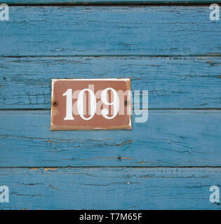 Number 109 on Blue painted wood - Stock Photo