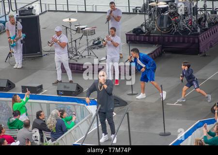Orlando, Florida. March 17, 2019. Alexander Delgado sings, while his son dances with Randy Malcom by Gente de Zona at Seaworld  in International Drive - Stock Photo
