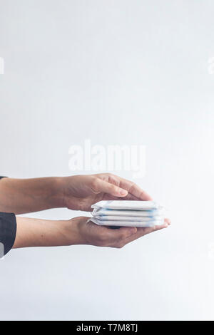 Female's hygiene products. Woman's hand holding a stack of sanitary napkins against the white background. Period days concept showing feminine menstru - Stock Photo