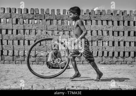 Kolkata : dated 04/02/2018, A village near brick kilin , people live in the mud houses, children play to run with waste tyre bear feet, small girls si - Stock Photo