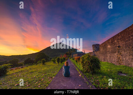 Api volcano at sunset, sitting woman looking at view from Banda Naira fort, Maluku Moluccas Indonesia, Top travel tourist destination, dramatic sky. - Stock Photo
