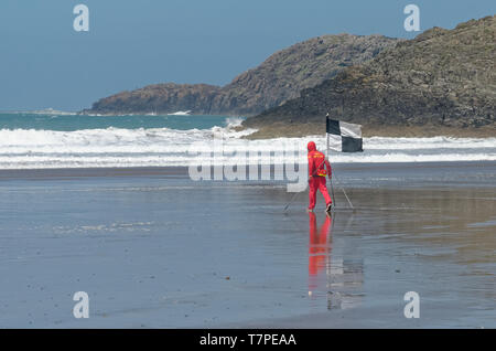 Surf lifesaving, Welsh style, as a lifeguard puts out the flags on a cold day at Whitesands Bay on the Pembrokeshire Coast Path in western Wales - Stock Photo