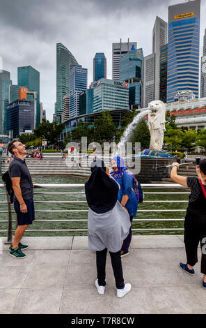 Tourists Posing For Photos In Front Of The Merlion Statue and Singapore Skyline, Singapore, South East Asia - Stock Photo