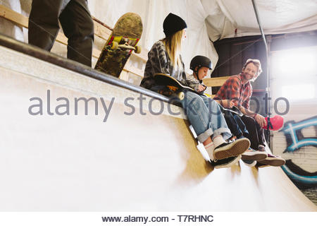 Family sitting at top of ramp at indoor skate park - Stock Photo