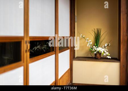 Traditional japanese house or ryokan with shoji sliding paper doors and ikebana decoration - Stock Photo