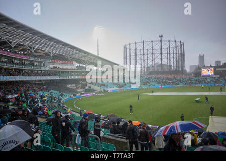 London, UK. 8th May 2019.  UK Weather: Ticket holders wait  under umbrellas as heavy rain and hail  stops play during the first One Day International between England and Pakistan at The Kia Oval.  Credit: Thomas Bowles/Alamy Live News - Stock Photo