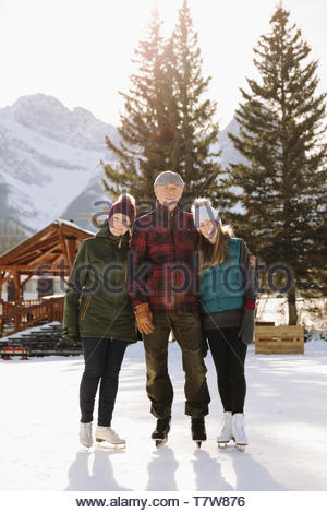 Portrait senior couple and daughter ice skating on frozen pond - Stock Photo