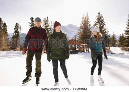 Senior couple and daughter ice skating on sunny, frozen pond - Stock Photo