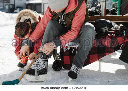 Father helping son tie ice skates, preparing for outdoor ice hockey - Stock Photo