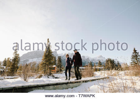 Senior couple walking along sunny, snowy path with mountains in background - Stock Photo