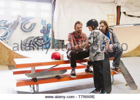 Father helping son skateboarding at indoor skate park - Stock Photo