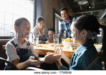 Cute sisters playing clapping game in restaurant - Stock Photo