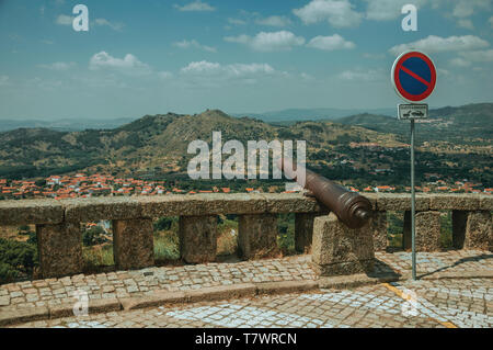 Old iron cannon over stone parapet and NO PARKING road sign overlooking hilly landscape at Monsanto. A cute and peculiar historic village of Portugal. - Stock Photo