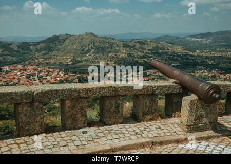 Old iron cannon over stone parapet overlooking hilly landscape with houses rooftops at Monsanto. A cute and peculiar historic village of Portugal. - Stock Photo