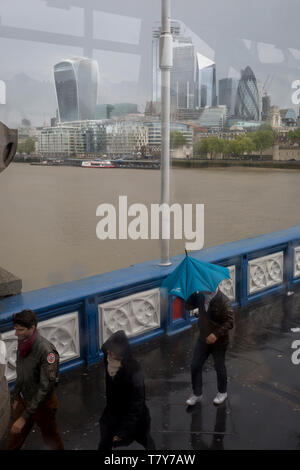 Tourists brave a wet and windy Tower Bridge, on Tower Bridge, on 8th May 2019, in London, England. - Stock Photo