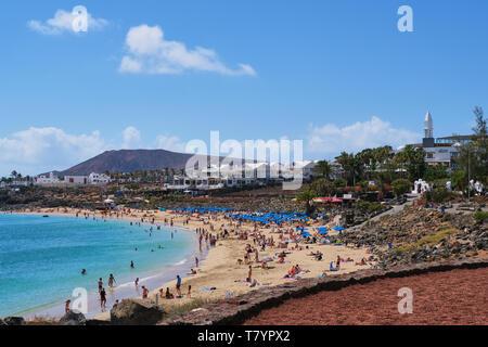 Playa Blanca, Lanzarote, Spain - April 24, 2019: tourists enjoy a day on the beach of Playa Dorada in Lanzarote, at wintertime a preferred destination - Stock Photo