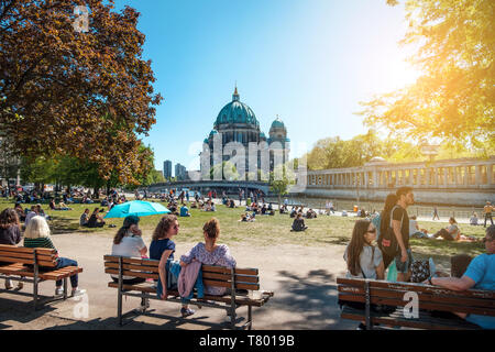 Berlin, Germany - April, 2019: People in public park on a sunny day near Museum Island and Berlin Cathedral - Stock Photo