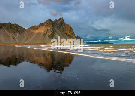 View of the mountains of Vestrahorn from black volcanic sand beach at sunset, Stokksnes, South Iceland, Iceland, Polar Regions - Stock Photo